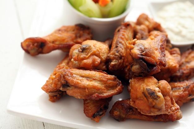 Alitas de pollo con salsa y verduras