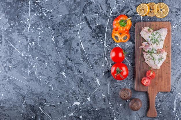 Alitas de pollo y tomates en rodajas sobre una tabla de cortar junto a una variedad de verduras en la superficie azul