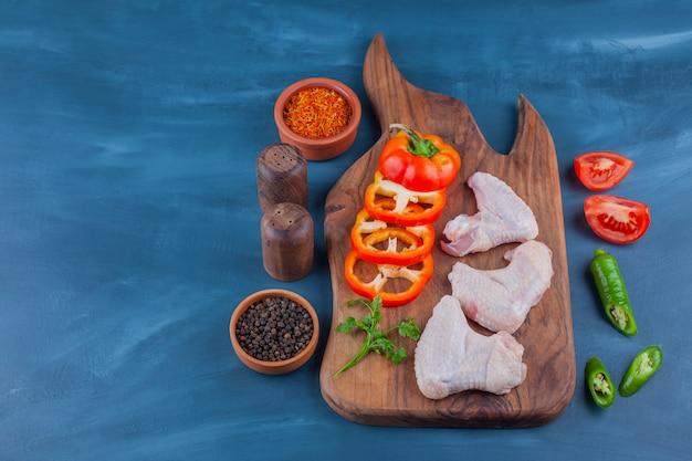 Alitas de pollo y verduras en rodajas sobre una tabla de cortar, sobre la mesa azul.