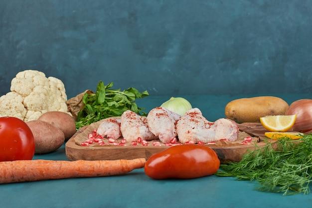 Alitas de pollo con verduras sobre una tabla de madera.