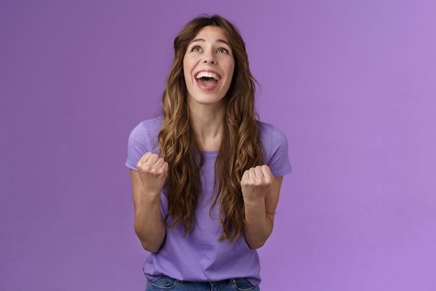 Aliviado niña feliz gracias a dios impresionante logro celebrar éxito implorar señor agradecido puño bomba gritando levantar cabeza arriba cielo triunfando buenas noticias stand fondo púrpura alegre reacción positiva
