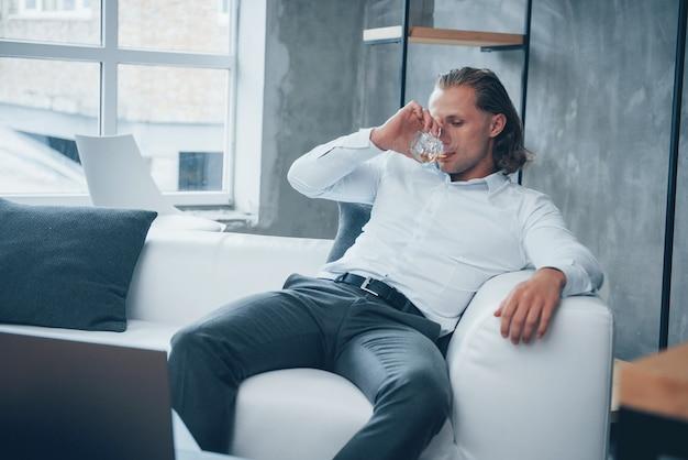 El alivio del estrés. joven sentado frente a un cuaderno y bebiendo whisky
