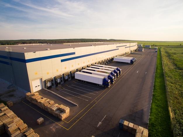 Almacén de distribución con camiones de diferente capacidad.