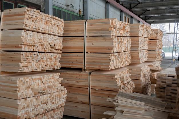 Almacén: palos de pino de madera rectangulares aserrados sujetados
