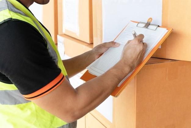 Almacén trabajador mano portapapeles inspeccionar los detalles de la lista de verificación del envío