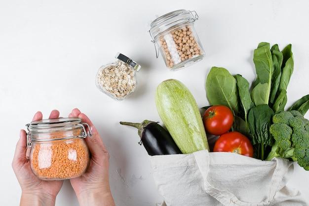 Almacenamiento de alimentos de desperdicio cero, vista superior ecológica. bolsa de algodón reutilizable con verduras y espinacas, tarro de cristal.