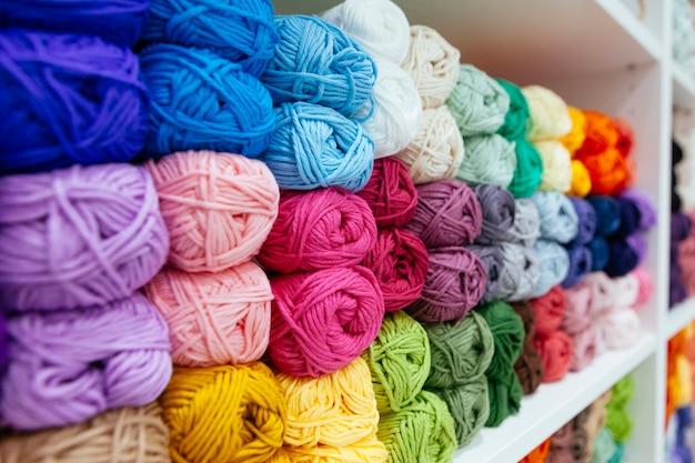 Almacenamiento de hilos de lana coloridos organizados por color en un estante