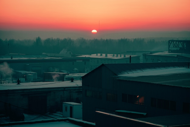 Almacenamiento de mercancías en almacenes en invierno al amanecer. vista desde arriba del área industrial en la salida del sol en tonos rosados. zona de edificios industriales de cerca con copyspace.
