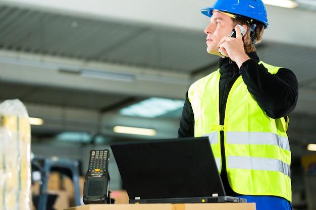 Almacenista con chaleco protector, escáner y computadora portátil en el almacén de la empresa de transporte de carga mediante un teléfono móvil