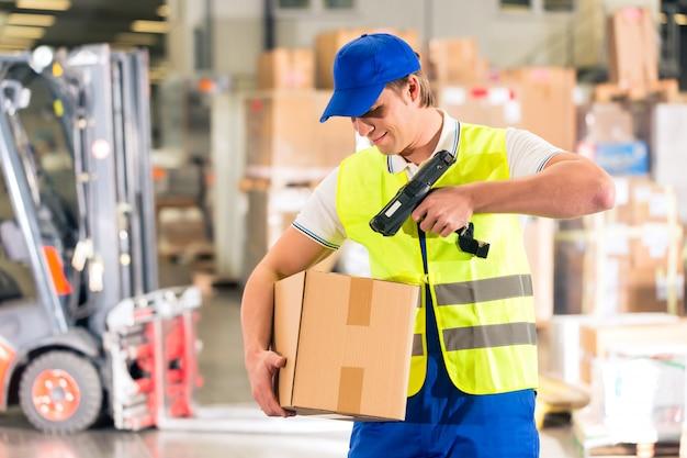 Almacenista con chaleco protector y escáner, escanea el código de barras del paquete, está parado en el almacén de la empresa de transporte de carga