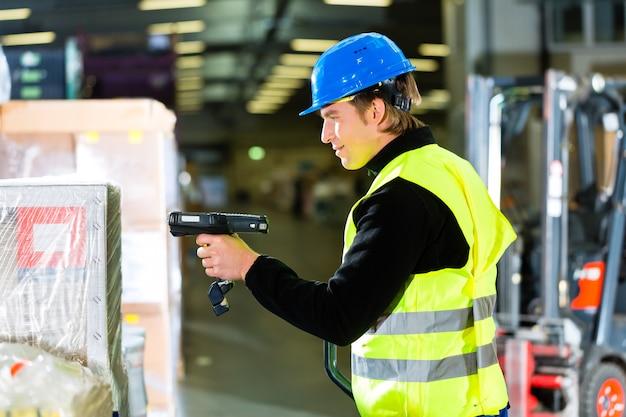 Almacenista en chaleco protector con un escáner, de pie junto a paquetes y cajas en el almacén de la empresa de transporte de carga, una carretilla elevadora