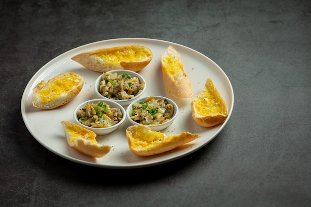 Almeja al horno con ajo y mantequilla servida con pan de ajo sobre fondo oscuro
