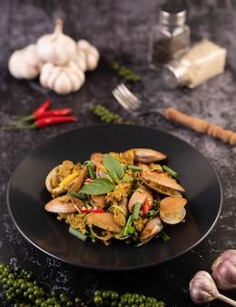 Las almejas frieron el curry en polvo en una placa negra.