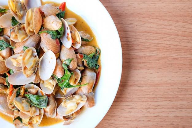 Las almejas salteadas en caliente con pasta de chile asado y albahaca sirven en un plato blanco sobre mesa marrón - concepto de comida casera.