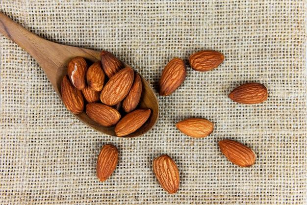 Almendras en la cuchara de madera y vista superior del saco / cerrar almendras nueces alimentos proteicos naturales y para la merienda