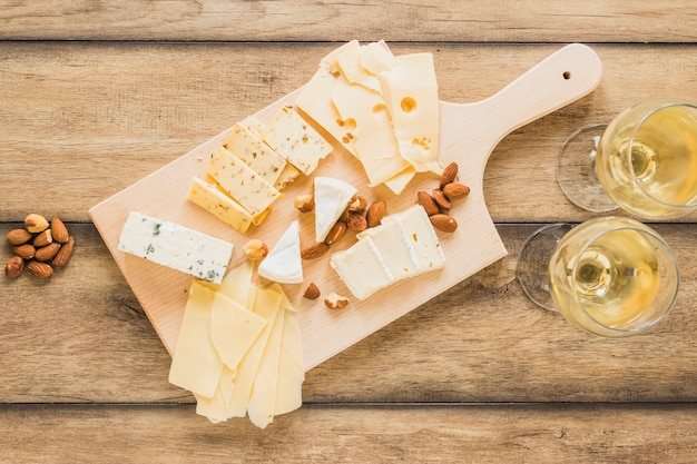 Almendras y diferentes tipos de queso con vino en mesa de madera.
