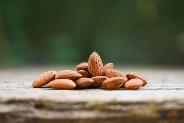 Almendras en la mesa de madera y naturaleza borrosa / cerrar almendras nueces alimentos proteicos naturales y aperitivos