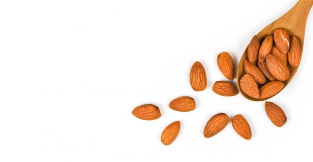 Almendras nueces en cuchara de madera / cerrar almendra aislado sobre fondo blanco.