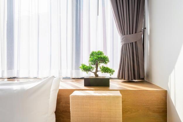 Almohada blanca en la decoración de la cama con lámpara de luz y árbol verde