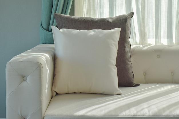Almohada blanca y negra en sofá beige con luz natural en la sala de estar