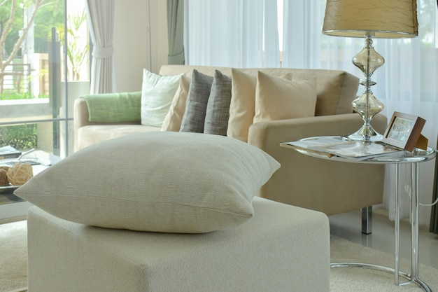 Almohada blanquecina en taburete en sala de estar interior moderna