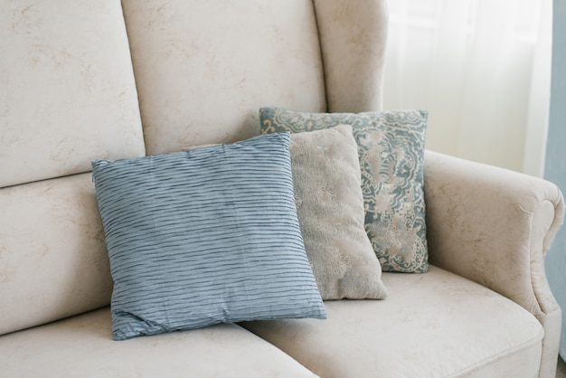 Almohadas azules y grises en el sofá de la sala de estar