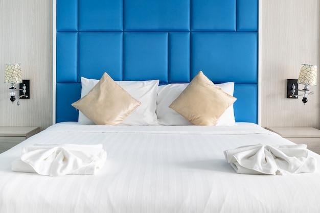 Las almohadas de la cama y la pareja en el dormitorio moderno decoran con tono de color azul