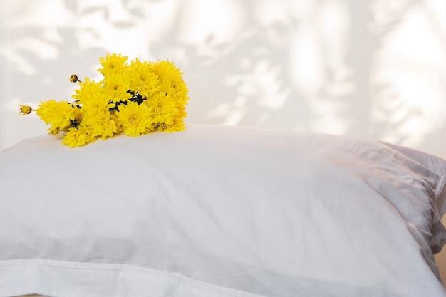 Almohadas y hermosa flor amarilla en la parte superior de la habitación de la cama.