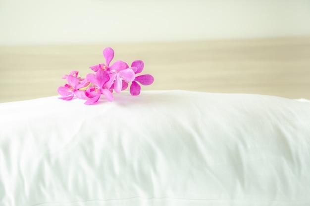 Almohadas y hermosas flores de orquídeas en la parte superior de la habitación con una suave niebla creativa