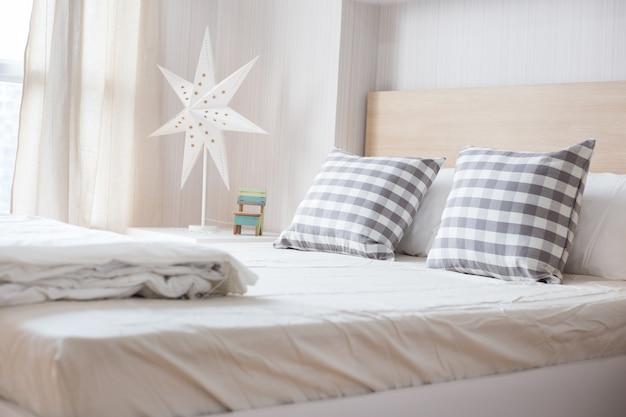 Almohadas de lujo en cama blanca en dormitorio