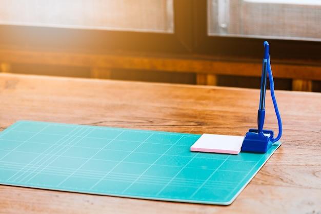 Almohadilla de corte con pin de papel y lápiz en la mesa en la sala vintage