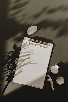 Almohadilla de portapapeles de hoja de papel en blanco, sombras de luz solar de flores, piedra, concha, coral en verde oscuro