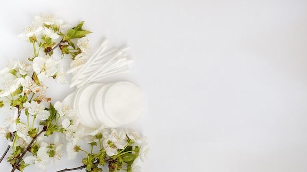 Almohadillas cosméticas higiénicas desechables y flor.