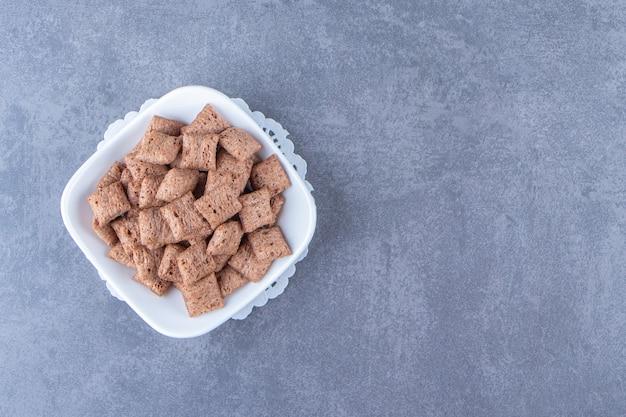 Almohadillas de maíz de chocolate en un tazón en una montaña rusa, sobre el fondo azul.