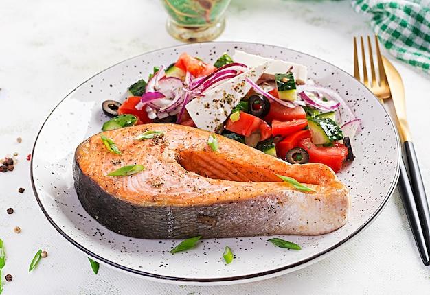 Almuerzo cetogénico. salmón al horno con guarnición de ensalada griega. cena saludable. dieta ceto / paleo.