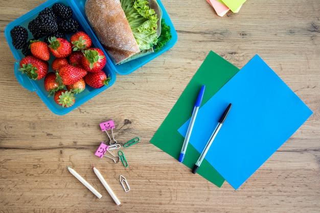 Almuerzo en contenedor y cuadernos en mesa.