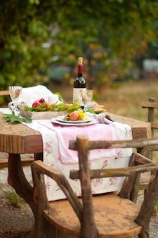 El almuerzo es romántico en el jardín de otoño, ambiente de vacaciones y comodidad. cena otoñal al aire libre con vino y fruta. mesa de decoración con flores y granadas. foto de época