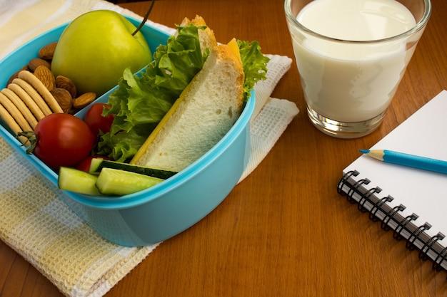 Almuerzo escolar en la caja, leche en el vaso y cuaderno sobre la mesa