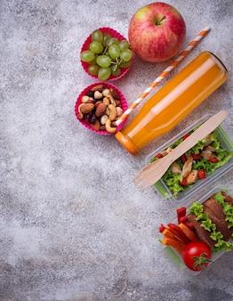 Almuerzo escolar. ensalada, sandwiches, frutas y frutos secos.