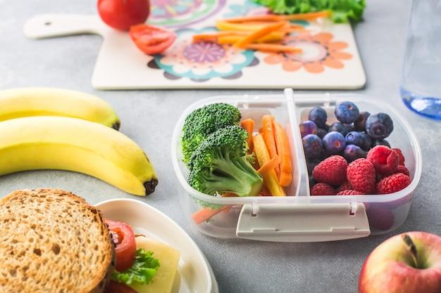 Almuerzo escolar con verduras bayas plátano en mesa gris saludable