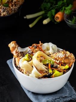 Almuerzo estilo asiático con fideos con pollo en salsa teriyaki, verduras, especias y microgreens