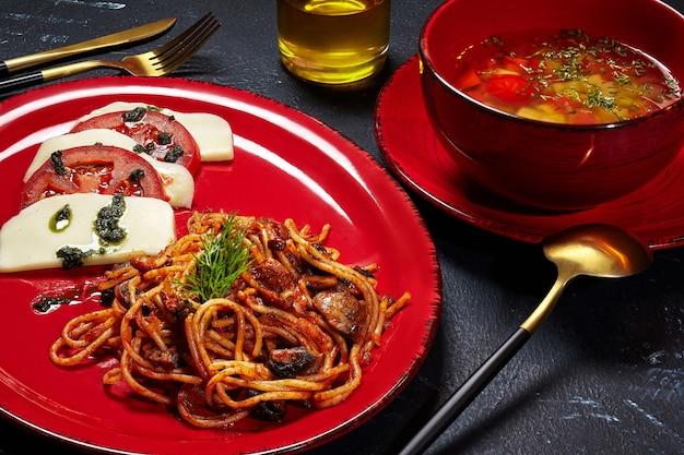 Almuerzo fijo de espaguetis de caldo de verduras con champiñones y ensalada caprese