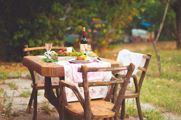 Almuerzo en el jardín con vino y fruta. cena romántica al aire libre. hojas de otoño de flores. hermosa mesa de scrapbooking. foto de época
