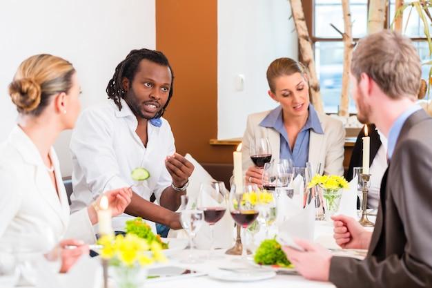 Almuerzo de negocios en restaurante con comida y vino.