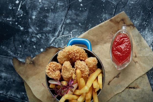 Almuerzo o merienda - tiras de pollo frito y papas fritas en una sartén de metal con salsa de tomate. papel artesanal en el espacio.