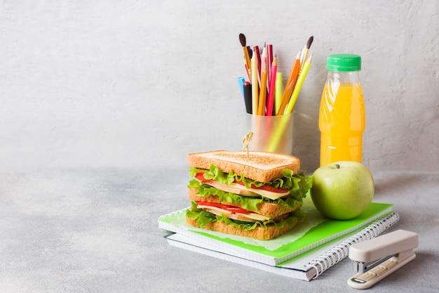 Almuerzo saludable para la escuela con sandwich, manzana fresca y jugo de naranja.
