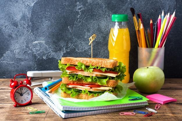 Almuerzo saludable para la escuela con sándwich, manzana fresca y jugo de naranja.