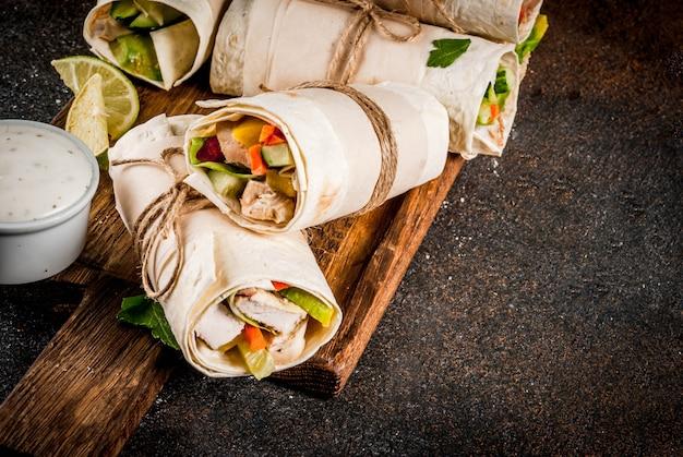 Almuerzo saludable merienda. pila de tortillas de fajita de comida callejera mexicana con filete de pollo a la parrilla y verduras frescas