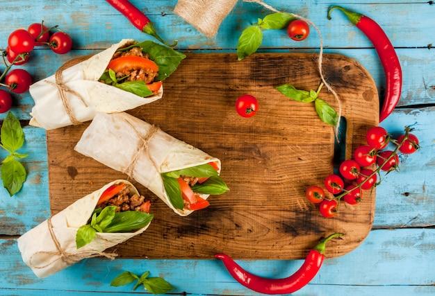 Almuerzo saludable merienda. sándwiches rollo retorcido tortilla con carne y verduras una tabla de cortar de madera sobre una mesa rústica de madera azul, espacio de copia, vista superior