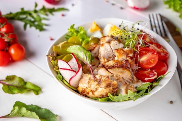 Almuerzo saludable en un tazón de buda con pollo al horno, quinua, tomates cherry, rábanos, huevos, pepinillos, pepinillos y rúcula
